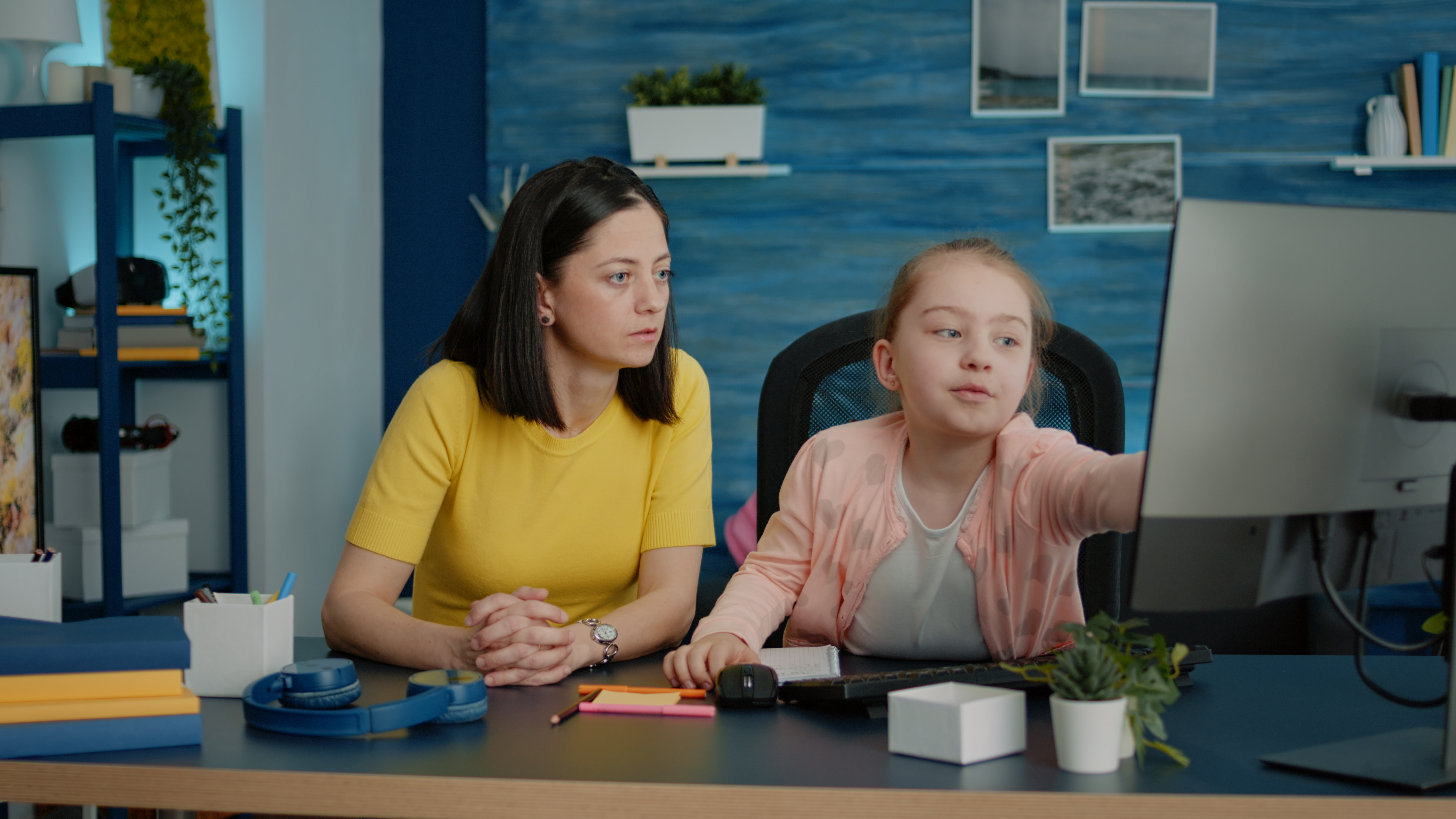 Young girl receiving help with homework from mother